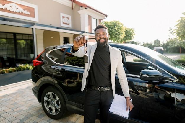 屋外の新しい黒い車のクロスオーバーの近くに車のキー立ってを示す幸せなアフリカ系アメリカ人の男。車のキーと車の販売契約を保持している若いアフリカ系アメリカ人実業家 Premium写真