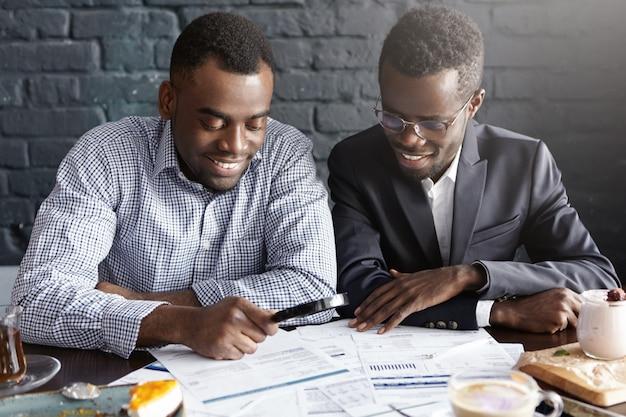 陽気なルックスのフォーマルな服を着て幸せなアフリカ系アメリカ人のオフィスワーカー 無料写真