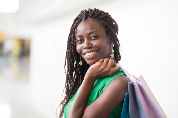 Happy african american woman with shopping bags Free Photo