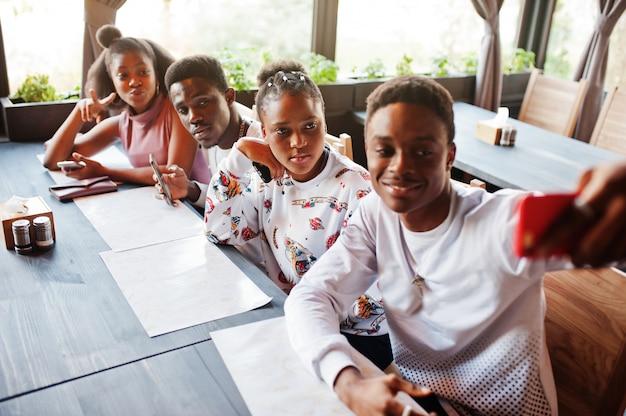 座っているとカフェでチャット幸せなアフリカの友人。レストランで出会い、携帯電話を見る黒人のグループ。 Premium写真