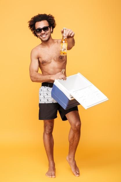 Счастливый африканский парень в солнцезащитные очки, положить бутылку пива в холодильник Бесплатные Фотографии