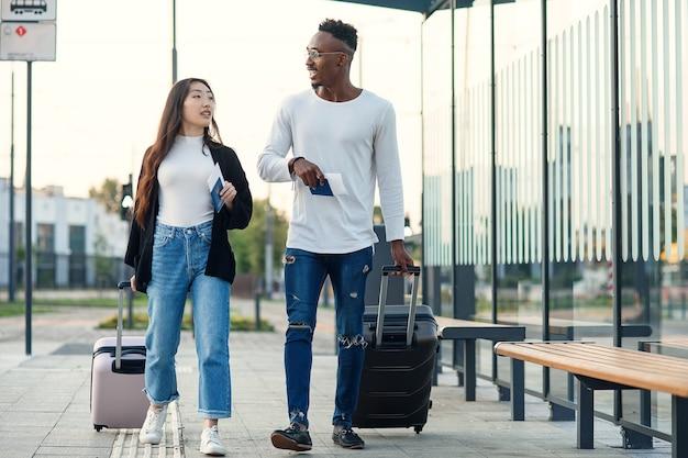 彼の笑顔のアジアの女性と幸せなアフリカの男-チケットとパスポートを保持し、空港の近くでスーツケースを運ぶ仲間。 Premium写真