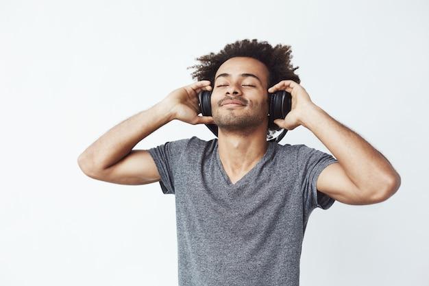 Прослушивание счастливого африканского человека усмехаясь к музыке в наушниках. Бесплатные Фотографии