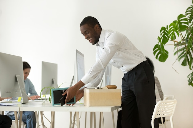 Happy african new employee unpacking belongings on first working day Free Photo