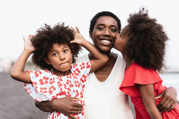 Happy african sister twins kissing mother on the beach - focus on mother face Premium Photo