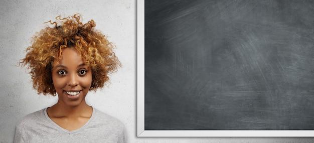 Felice studente africano con acconciatura afro in piedi isolato contro lavagna vuota con copia spazio per il contenuto pubblicitario con espressione gioiosa, ottenendo a a lezione di matematica Foto Gratuite