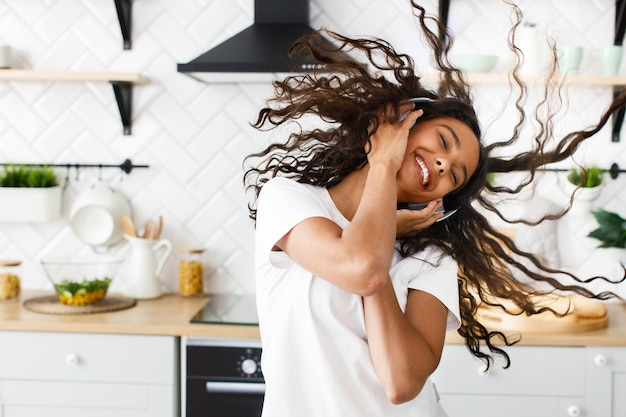 Happy african woman twirls her hair and listens to music via headphones in the kitchen Free Photo