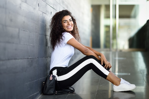 Happy african woman with black curly hairstyle sitting on urban floor. Premium Photo