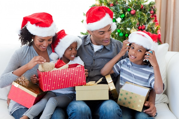 Happy afro-american family playing with christmas presents Premium Photo