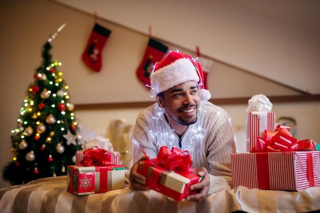Счастливый афро американец с рождеством шляпу и подарки вокруг. Premium Фотографии