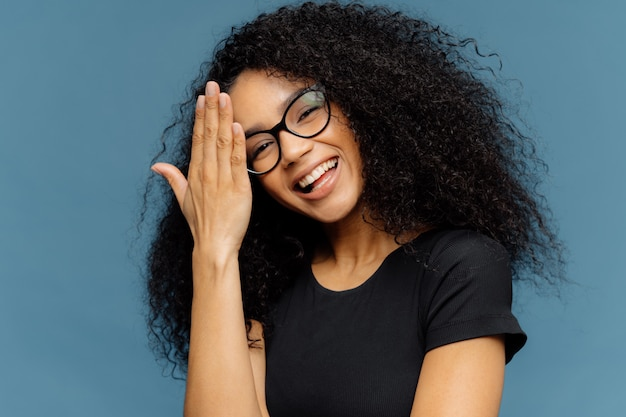 Happy afro american woman touches forehead, tilts head, smiles happily at camera Premium Photo