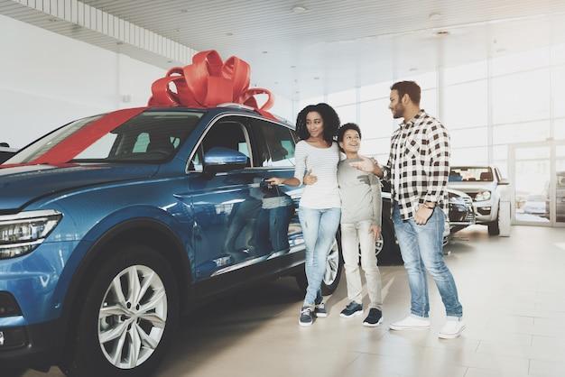 Happy afro woman opens car door in auto salon. Premium Photo