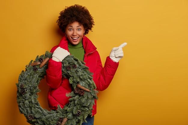 Счастливая афро-женщина показывает путь к своему дому, носит красное пальто, белые перчатки, несет рождественский венок, указывает на пустое место, стоит на желтом фоне Бесплатные Фотографии