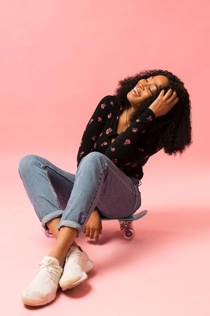 Happy afroamerican lady sitting on skateboard Free Photo