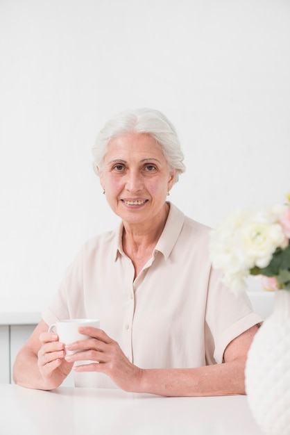 Happy aged woman holding white cup of coffee Free Photo