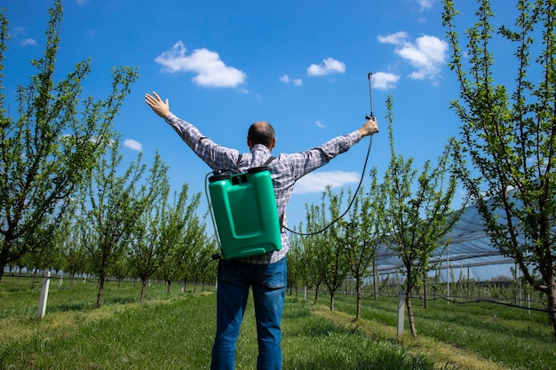 Happy agronomist farmer with sprayer and raised hands celebrating success in apple fruit orchard Free Photo