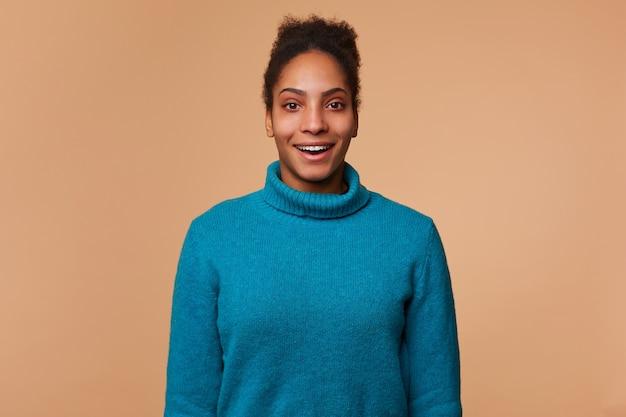 Счастливая изумленная афроамериканка в синем свитере с вьющимися темными волосами услышала о сумасшедших скидках. улыбается и выглядит изолированным. Бесплатные Фотографии