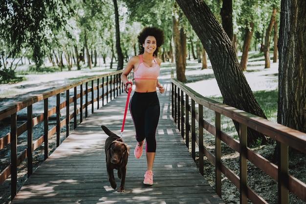 Happy american woman jogging on footbridge Premium Photo