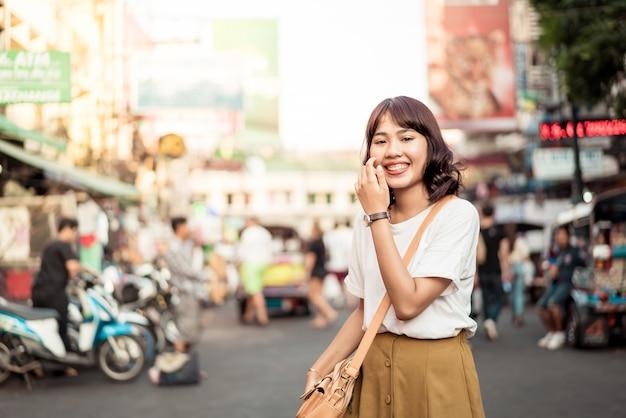 幸せで美しいアジアの女性がタイのカオサーンロードを旅行 Premium写真