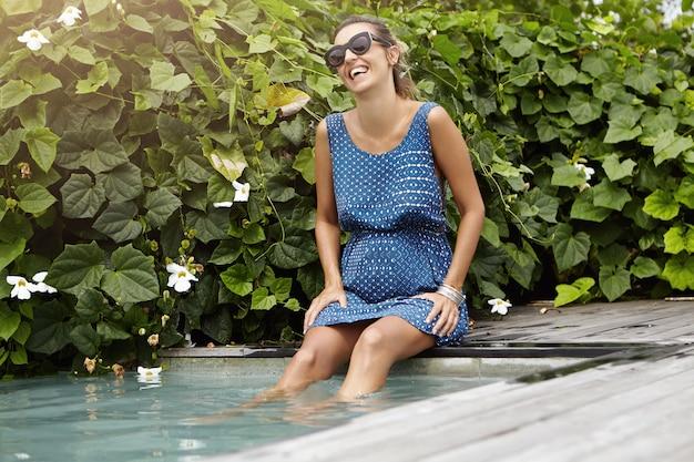 Счастливая и жизнерадостная будущая мама в синем летнем платье и модных солнцезащитных очках отдыхает в бассейне с ногами под водой Бесплатные Фотографии