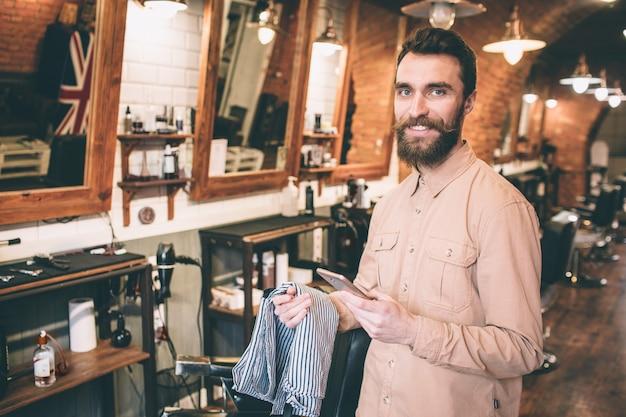 Счастливый и веселый парень стоит в парикмахерской и смотрит в камеру. он улыбается человек держит прикрытие для плеч клиента. Premium Фотографии