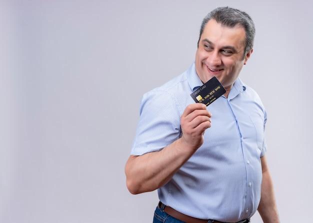 クレジットカードoaホワイトスペースを保持している青いシャツを着て満足して満足している中年男 無料写真