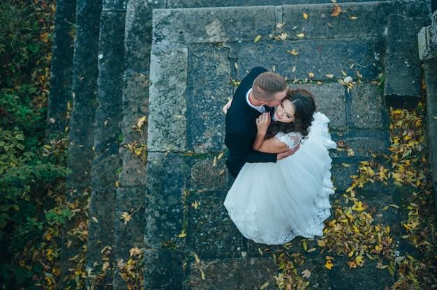 Счастливые и влюбленные невеста и жених гуляют в осеннем парке в день свадьбы Premium Фотографии