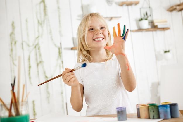 행복하고 쾌활한 귀여운 주근깨 금발 소녀 흰색 옷을 입고 한 손으로 브러시를 잡고 다른 손을 보여주는, 그녀는 페인트로 엉망. 무료 사진