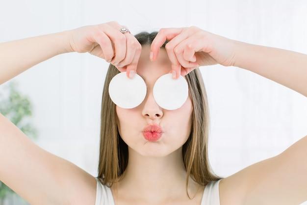 Счастливые и позитивные молодая красивая женщина с открытыми плечами, закрыв глаза с ватные диски и показывая поцелуй губы на светлом фоне. уход за кожей и концепция красоты Premium Фотографии