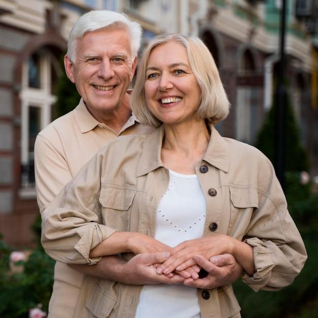 Счастливая и улыбающаяся старшая пара позирует вместе во время прогулки по городу Бесплатные Фотографии