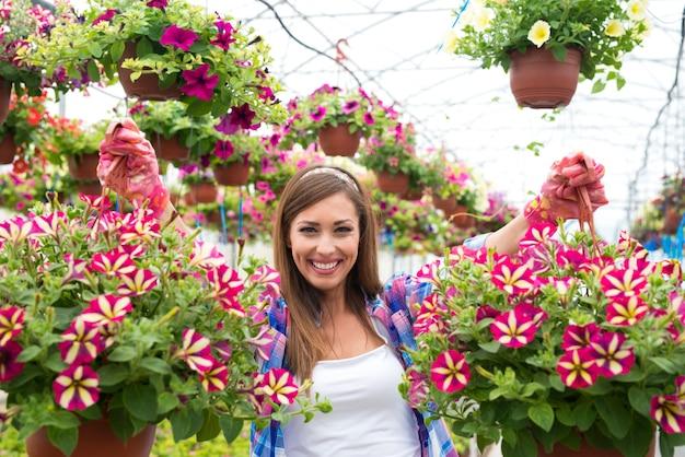 温室ガーデンセンターで花束の花の植物を保持している幸せで笑顔の女性の花屋 無料写真