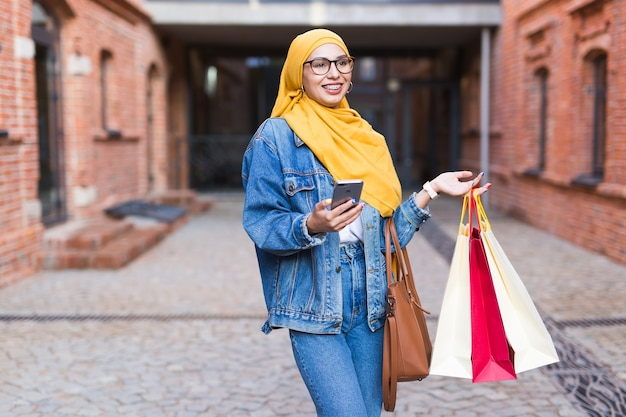 Happy arab muslim girl with shopping bags Premium Photo
