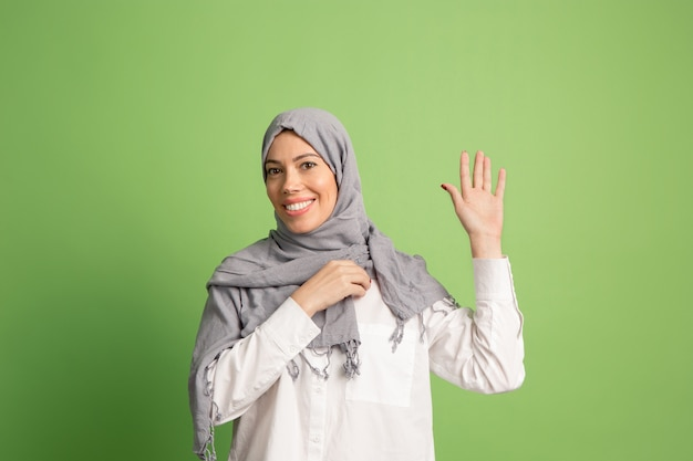 Happy arab woman in hijab. portrait of smiling girl, posing at green studio background. Free Photo
