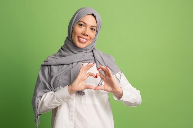 Happy arab woman in hijab. portrait of smiling girl, posing at green studio. Free Photo