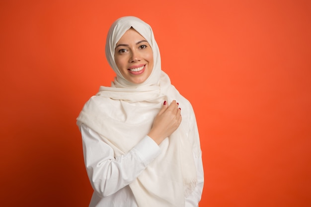 Happy arab woman in hijab. portrait of smiling girl, posing at red studio background. young emotional woman. the human emotions, facial expression concept. front view. Free Photo