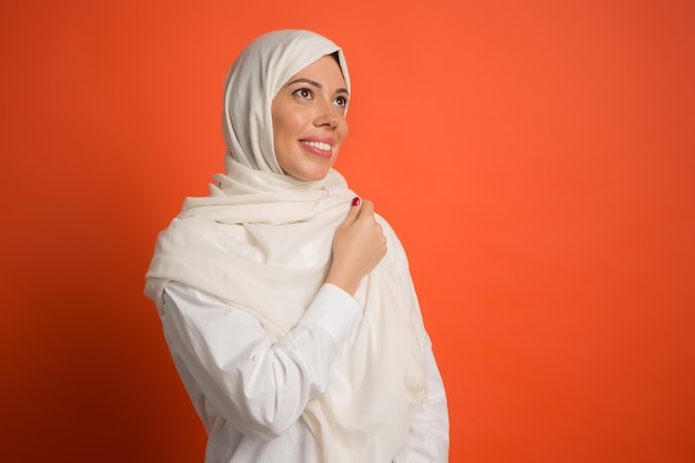 Happy arab woman in hijab. portrait of smiling girl, posing at red studio background. young emotional woman. human emotions, facial expression concept. Free Photo
