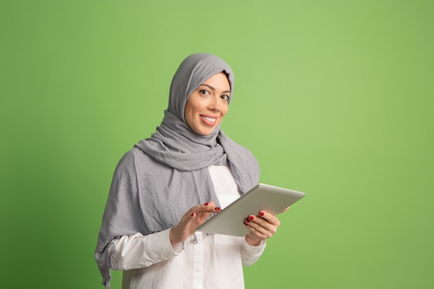 Happy arab woman in hijab with laptop. portrait of smiling girl, posing at green studio background. young emotional woman. the human emotions, facial expression concept. front view. Free Photo