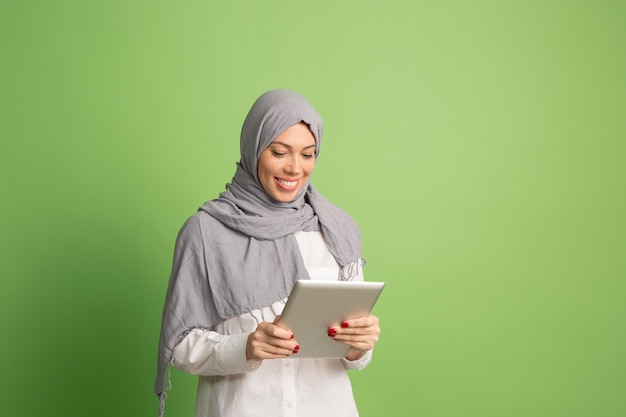 Happy arab woman in hijab with laptop. portrait of smiling girl, posing at green studio. Free Photo