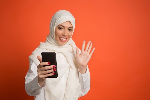 Happy arab woman in hijab with mobile phone making selfie. Free Photo