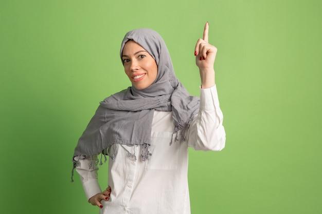 ヒジャーブの幸せなアラブの女性。緑のスタジオの背景でポーズをとって、笑顔の女の子の肖像画。 無料写真