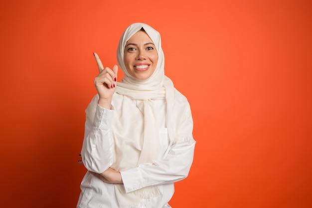 Счастливая арабская женщина в хиджабе. портрет улыбающейся девушки, позирующей на красном фоне студии. Бесплатные Фотографии