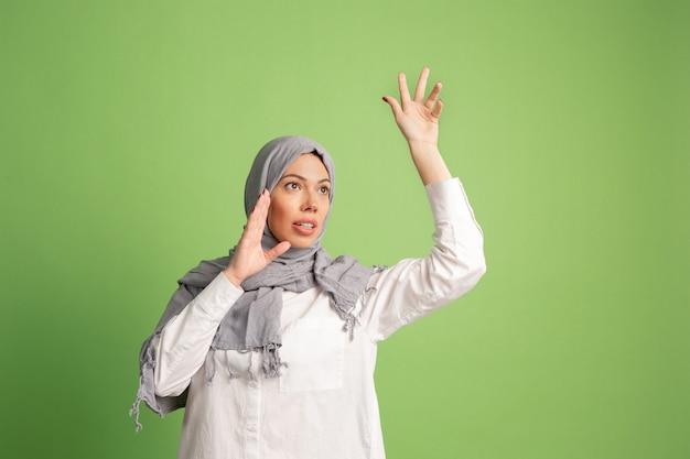 ヒジャーブの幸せなアラブの女性。緑のスタジオの背景で叫んで、笑顔の女の子の肖像画。若い感情的な女性。人間の感情、表情の概念。正面図。 無料写真