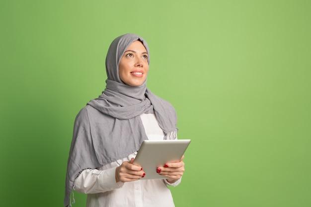 ラップトップとヒジャーブで幸せなアラブの女性。緑のスタジオの背景でポーズをとって、笑顔の女の子の肖像画。若い感情的な女性。人間の感情、表情の概念。正面図。 無料写真