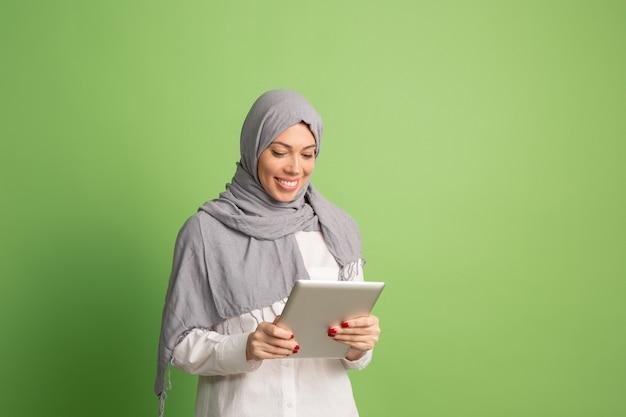 Счастливая арабская женщина в хиджабе с ноутбуком. портрет улыбающейся девушки, позирующей в зеленой студии. Бесплатные Фотографии