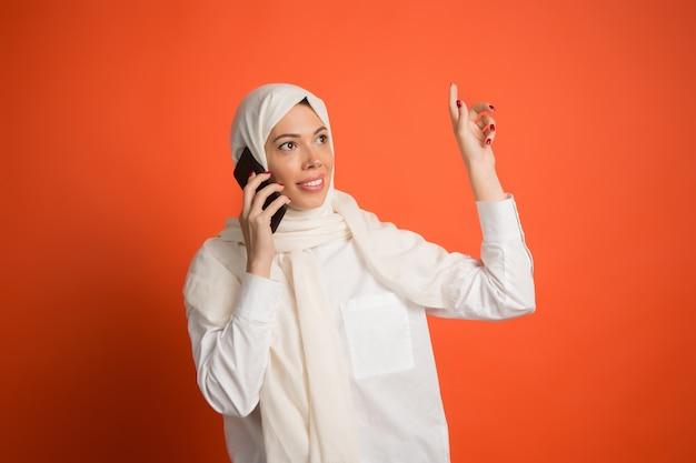 携帯電話でヒジャーブの幸せなアラブの女性。赤いスタジオの背景でポーズをとって、笑顔の女の子の肖像画。 無料写真