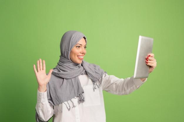 タブレットとヒジャーブで幸せなアラブの女性。緑のスタジオの背景でポーズをとって、笑顔の女の子の肖像画。 無料写真