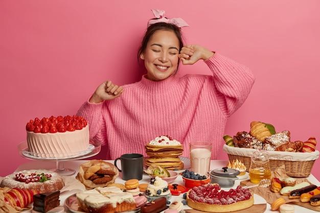 La ragazza asiatica felice di compleanno arriva al tea party, mangia dolci deliziose torte, circondata da molti dessert, pone su sfondo rosa. Foto Gratuite