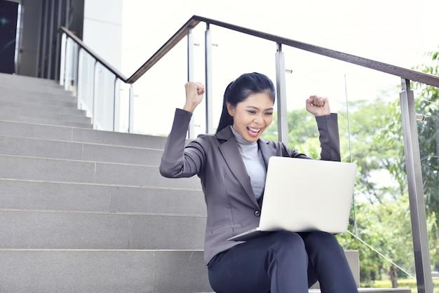 Happy asian businesswoman with laptop working Premium Photo