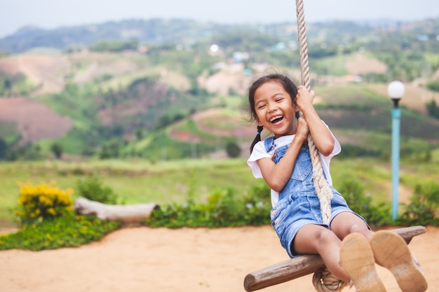 Happy asian child girl having fun to play on wooden swings in playground Premium Photo