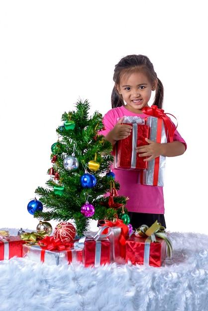Happy asian child holding christmas presents. Premium Photo